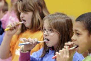 """(B27)  ** ADVANCE FOR SUNDAY, MARCH 1 ** Students prepare to brush their teeth for two minutes at Park Elementary School in Columbia, Pa. on Wednesday, Feb. 11, 2009. As part of National Children's Dental Health Month, St. Joseph Health Ministries held a """"2 for 2"""" event at the school, encouraging kids to brush twice a day for two minutes at a time. (AP Photo/Lancaster New Era, Marty Heisey)"""