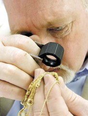 Herald & Review/Kelly J. Huff Jeff Parsons, owner of Antique Treasure Hunters Road Show looks to determine the karat content of a gold chain during an open house at the Decatur Hotel and Conference Center.